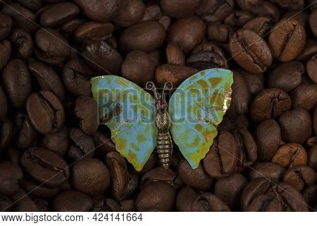 A Butterfly Brooch Lies On The Scattered Coffee Beans.