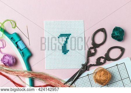 Green Number 7 Cross-stitch Embroidered Surrounded By Accessories For Embroidery: Threads Of Moulin