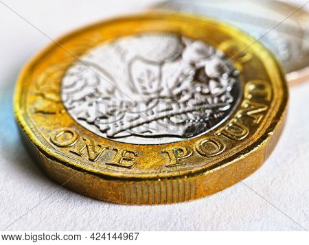 One British Pound Coin Lies On A Light White Textured Surface. Focus Is On Denomination Of Coin And