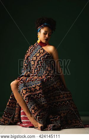 African American Woman With Colorful Headscarf Sitting Wrapped In Ornament Blanket On Dark Green