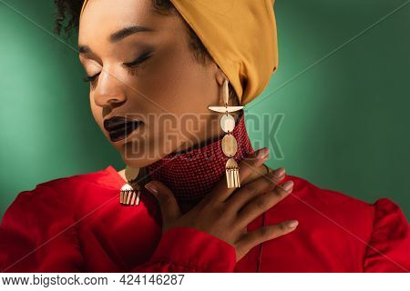 Young African American Woman In Headscarf Touching Neck With Closed Eyes On Green
