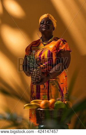 Confident Middle Aged African American Saleswoman Standing Near Fruits With Pineapple In Hands On Or