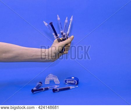 Female Hand Holding Plastic Syringes With Gel For Teeth Whitening With Blue Led Lamp And Mouth Tray
