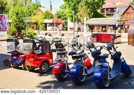 Palanga, Lithuania -14th June, 2021: Many Colorful Fat Tyre Electric Scooters Parked For Rent In Pub