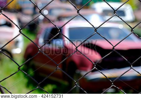 Old car dump filled with wrecked cars broken glass parts