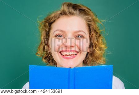 Smiling Teacher In Classroom. Female Lecturer With Book. School Subjects. Education.