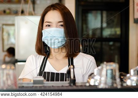 A Beautiful Asian Female Employee Wearing A Mask And An Apron. Standing At The Coffee Counter Ready