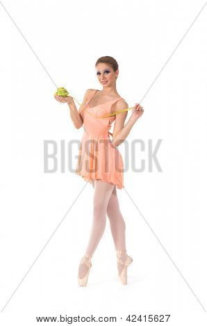 Young and beautiful ballerina dancing with a measuring tape and apple over white background