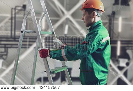 A Male Worker On Construction Site Holding And Carrying The Ladder