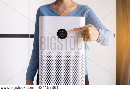 Women Hands Pointing To Screen Of White Modern Air Purifier In A Living Room For Refresh Air Flow At