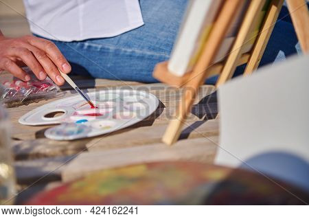 Close-up Of Female Painter Taking Paint With Paintbrush And Painting Outdoors. Open Air. Watercolor