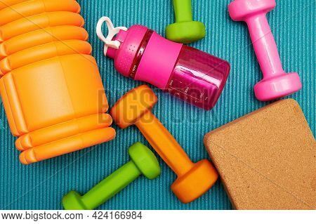 Scattered Fitness Objects, Dumbbells, Bricks And Bottle On The Mat In The Gym. Bodycare And Exercisi