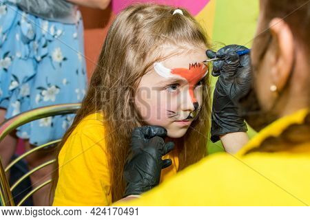 The Child Draw The Face On The Childrens Holiday. Aqua Make-up For Girls. Kids Party. The Girl Paint