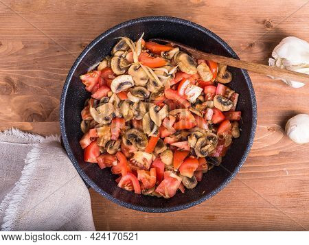 Champignon Mushrooms Cut Into Slices With Onions And Tomatoes Are Fried In A Pan. Frying Pan With Co