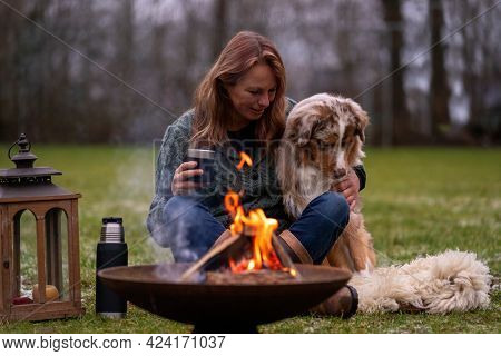 Dog Sits By The Fire With The Hosts And Huskyaustralian Shepherd Sits Next To His Owner By The Fire.