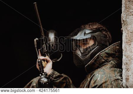 Portrait Of Young Man With Protective Mask, Paintball Gun And Camouflage Wear, Ready For An Action P