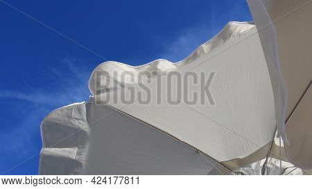 Fluttering Frills Of White Textile Umbrellas Against Blue Sky Background With Copy Space. View From