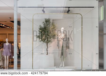 A Window Glass Case In The Shop With Manequins Showing New Clothes