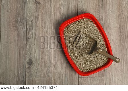 Cat Tray With Clumping Litter And Scoop On Wooden Floor, Top View. Space For Text