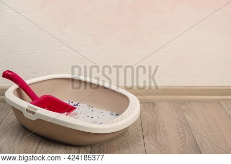 Cat Tray With Crystal Litter And Scoop On Floor Near Pink Wall. Space For Text