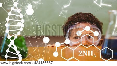 Composition of dna strand and elemental diagrams over child wearing safety glasses in science class. school, education and study concept digitally generated image.