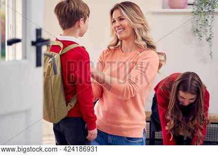Mother Helping Children In Uniform To Get Ready To Leave Home For School