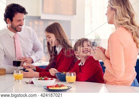 Parents Having Breakfast With Children In School Uniform At Kitchen Counter