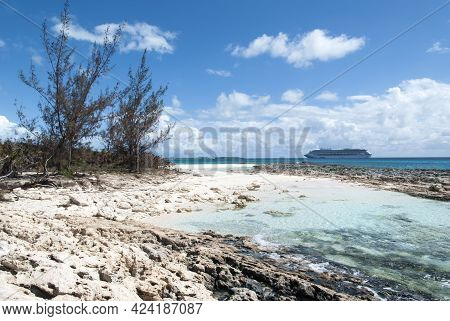 The View Of A Rocky Beach On Half Moon Cay And A Cruise Ship In A Background (bahamas).