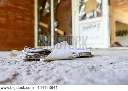 An Old Paper Visitor Log Lies On The Concrete Floor In Front Of A Brick Building