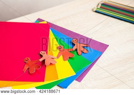 Figures Of People Made Of Paper, Holding Hands. Origami From Colored Paper.  Gays, Lesbians, Transge