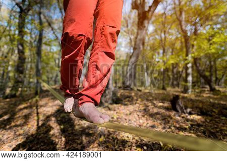 Close-up Below The Waist Of A Sporty Man Practicing Slackline Balance In Autumn Forest