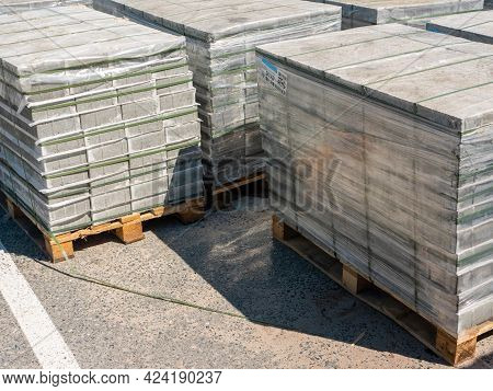 Noyabrsk, Russia - June 5, 2021: Paving Slabs Standing On A Wooden Pallet In A Film On The Asphalt.