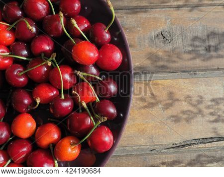 Cherry Background. Juicy Ripe Delicious Cherry Or Sweet Cherry Close-up From Above On A Dark Plate A