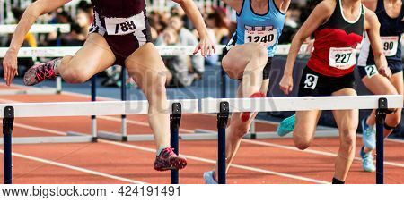 Front View Of Four High School Girls Running In A Hurdle Track And Field Race.