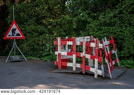 Road Work Sign Under Construction.caution Symbol. Red And White Triangle Safety Sign And Barriers Wa