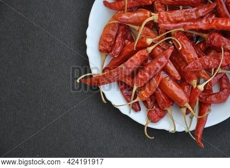 High Angle Of Heap Of Red Chilli Peppers On The White Plate Isolated Over Black Background