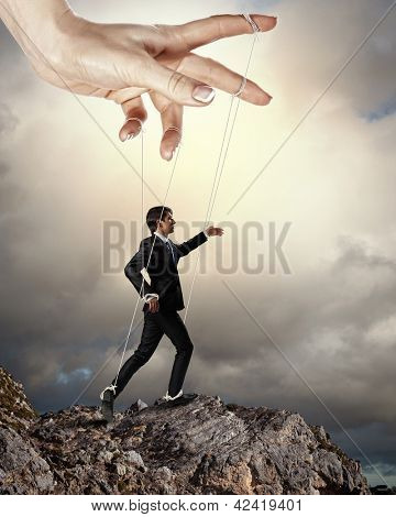Businessman marionette on ropes controlled by puppeteer standing atop of mountain