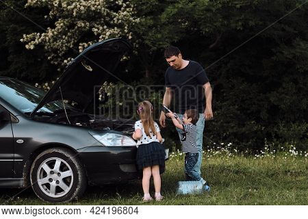Young Mechanic Dad Teaches His Son And Daughter To Repair Car. Father Opened The Hood Of Car And Sho