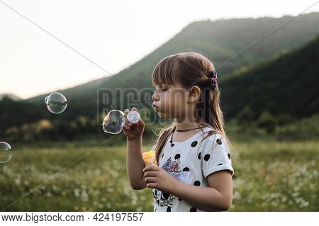 Little Girl In Dress Stands In Chamomile Field And Blows Soap Bubbles. Happy Childhood In Nature Amo