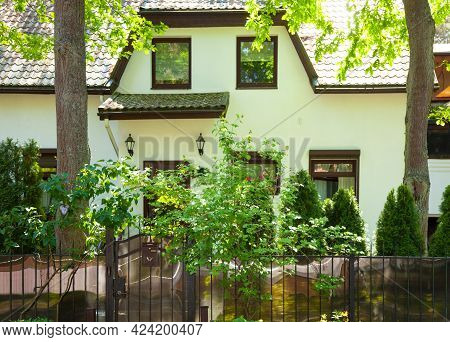 Detached Suburban House In The Garden. Front View.
