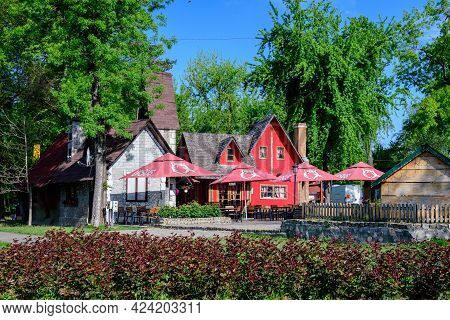 Mogosoaia, Romania - 7 May 2021: Vivid Red And White Wooden Houses In Mogosoaia Park In A Sunny Spri