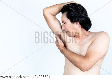 Portrait Images Of Asian Middle-aged Man Was Sniffing The Stench From His Armpit, On White Backgroun