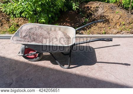 An Old One-wheel Wheelbarrow Is Filled With Construction Sand Mixture. There Is A Shadow On The Trac