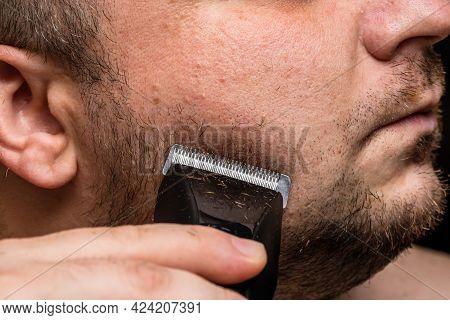 Man Shaving Or Trimming His Beard Using A Hair Clipper