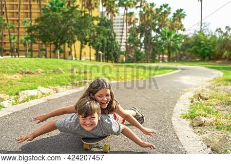Adorable Happy Kids Having Fun With Longboard In Park. Brother And Sister Lying On Their Skateboard.