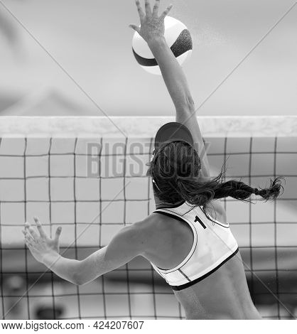 A Beach Volleyball Player Is Jumping At The Net And Spiking The Ball Down In Vertical Black And Whit