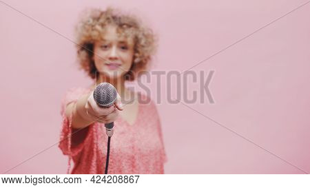 Beautiful Young Girl Holding Microphone Towards The Camera. The Focus Is On The Mic While The Girl I