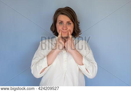 Upset Woman Making Fake Smile With Her Fingers Stretching The Corners Of Her Mouth