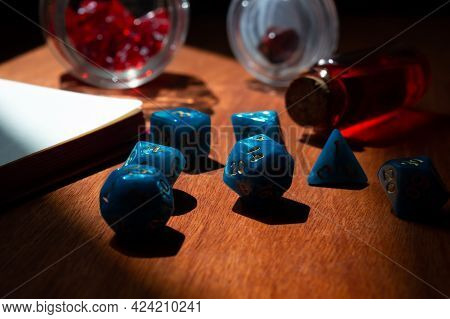 Close-up Image Of Blue Marbled Role-playing Gaming Dice On A Red Wooden Surface In The Sunlight.