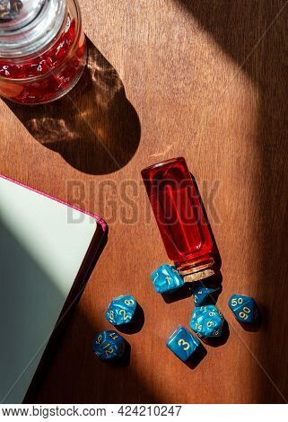 Vertical Overhead Image Of A Set Of Blue Marbled Role-playing Dice, A Glass Bottle With Red Liquid,